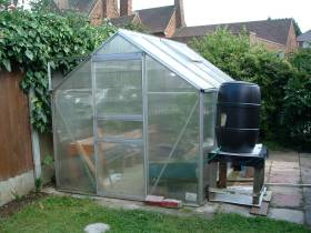 The plastic greenhouse with water butt for topping up automatically.